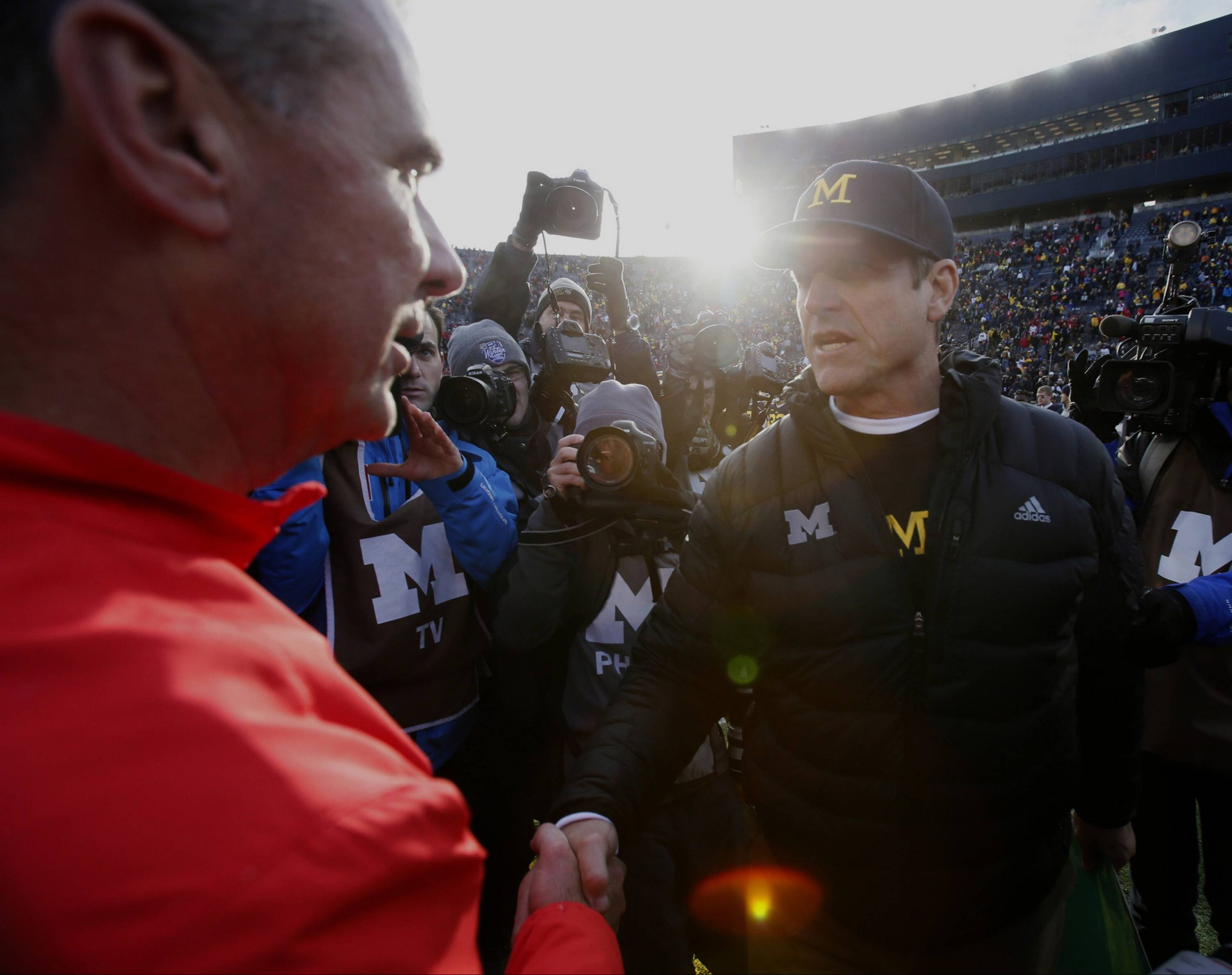 Michigan head coach Jim Harbaugh right shakes hands with Ohio Urban Meyer