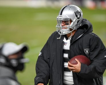 DENVER, CO - JANUARY 03: Las Vegas Raiders quarterback Marcus Mariota (8) holds a ball in the bench area during a game b