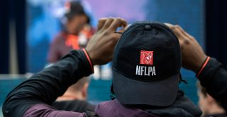 INDIANAPOLIS IN MARCH 02 A Scouting Combine participant takes a photo of his college teammate on